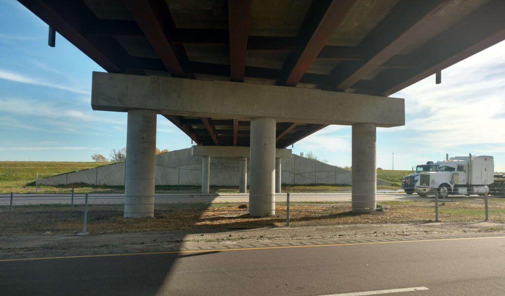 Underside of interstate bridge focusing on bridge piers and continuous welded plate girders.
