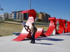 """A young skateboarder tries out the skateable """"WOW"""" sculpture in the park."""